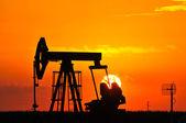 Jack olejové čerpadlo je ozářená zapadajícího slunce — Stock fotografie