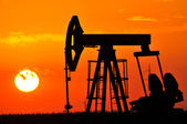 An oil pump jack is silhouetted by the setting sun — 图库照片