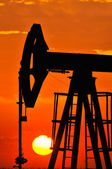 An oil pump jack is silhouetted by the setting sun — Photo