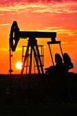 An oil pump jack is silhouetted by the setting sun — Stockfoto