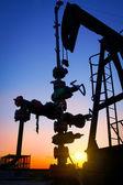 Eine öl-pumpe-buchse ist durch die untergehende sonne silhouetted — Stockfoto