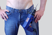 A man in jeans with a drill — Stock Photo