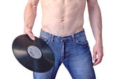 A man in jeans holding a phonograph record — Stock Photo