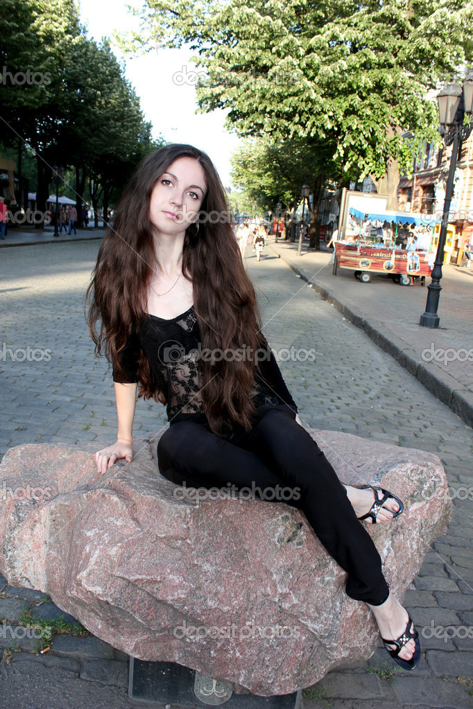 A girl with long hair sitting on a rock in the city. — Stock Photo #11367086