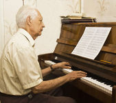 Old man playing piano — Stock Photo