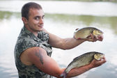Happy angler with two freshwater chubs. — Stock Photo