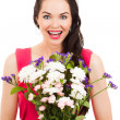 Surprised woman holding flowers — Stock Photo