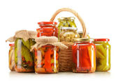 Composition with wicker basket and jars of pickled vegetables. — Stock Photo