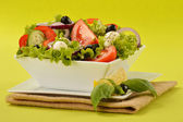 Vegetable salad bowl on green background — Stock Photo