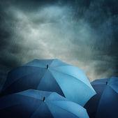 Dark clouds and umbrellas — Stock Photo