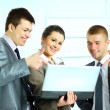 Young businesswoman with her colleagues using laptop — Stock Photo