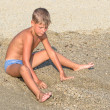 Royalty-Free Stock Photo: Boy playing in the sand on the beach