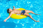 Boy floating on an inflatable circle in the pool. — Stockfoto