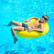 Boy floating on an inflatable circle in the pool. — Stock Photo