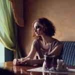 Fine art photo of a gorgeous brunette woman sitting alone — Stock Photo