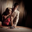 Young man & woman playing poker in casino — Stock Photo