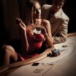 Stock Photo: Young man & woman playing poker in casino