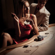 Young man &amp;amp; woman playing poker in casino - Stock Photo