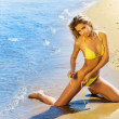 Beautiful sexy young tanned blond girl in bikini on the beach — Stock Photo