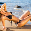 Young beautiful sexy blonde bikini model, laying on sea beach - Stock Photo
