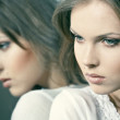 Face of a beautiful girl with her reflection in the mirror — Stock Photo