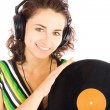Stock Photo: Beautiful young smiling women DJ listening music in headphones and holding vinyl plate