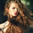 Summer portrait of a beautiful young Caucasian girl with curly hair — Stock Photo