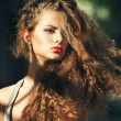 Summer portrait of a beautiful young Caucasian girl with curly hair - Stock Photo