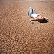 Stock Photo: Young woman lying in the middle of a desert.