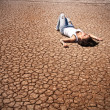 Young woman lying in the middle of a desert. — Stock Photo