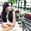 Young woman in a cafe outdoors - Stock Photo