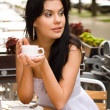 Royalty-Free Stock Photo: Young woman drinking tea in a cafe outdoors