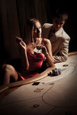 Young man & woman playing poker in casino — Foto de Stock