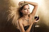 Retrato de estudio de una hermosa joven rubia que sostiene un vaso — Foto de Stock