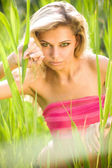 Sexy young blond woman in green grass — Stock Photo