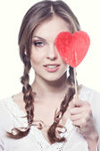 Lovely girl with a heart-shaped candy — Stock Photo