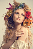 Stylized summer portrait of a young beautiful woman with flowers — Stock Photo