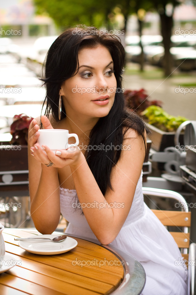 Young woman drinking tea in a cafe outdoors  Stock Photo #11699732