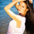 Beautiful sensual brunette girl standing in blue water - Stock Photo