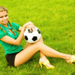 Beautiful girl with a classical soccer ball sitting on the grass — Stock Photo
