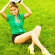 Stock Photo: Beautiful girl with a classical soccer ball sitting on the grass