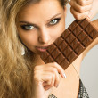 Close-up studio portrait of a beautiful young woman eating choco — Photo