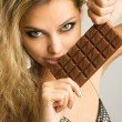 Close-up studio portrait of a beautiful young woman eating choco - Stock Photo