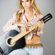 Studio portrait of a beautiful sexy young woman with black guitar — Stock Photo