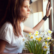 Beautiful young woman looking through a window — Stock Photo