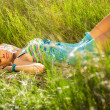 Beautiful young woman relaxing in the grass — Stock Photo