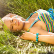 Beautiful young woman relaxing in the grass — Stock Photo #11895589