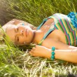 Stock Photo: Beautiful young woman relaxing in the grass