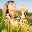 Attractive young girl relaxing on a meadow, holding dandelion flower — Foto de Stock