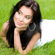 Beautiful young brunette girl on a lawn - Foto Stock